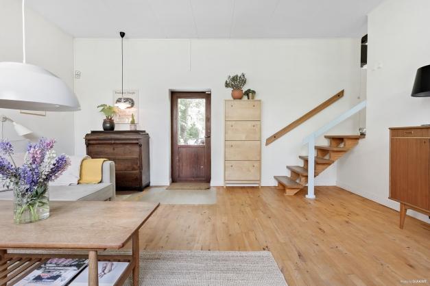 Från hallen finns en liten trappa med nedgång till husets allrum med parkettgolv i björk samt utgång till trädgården.