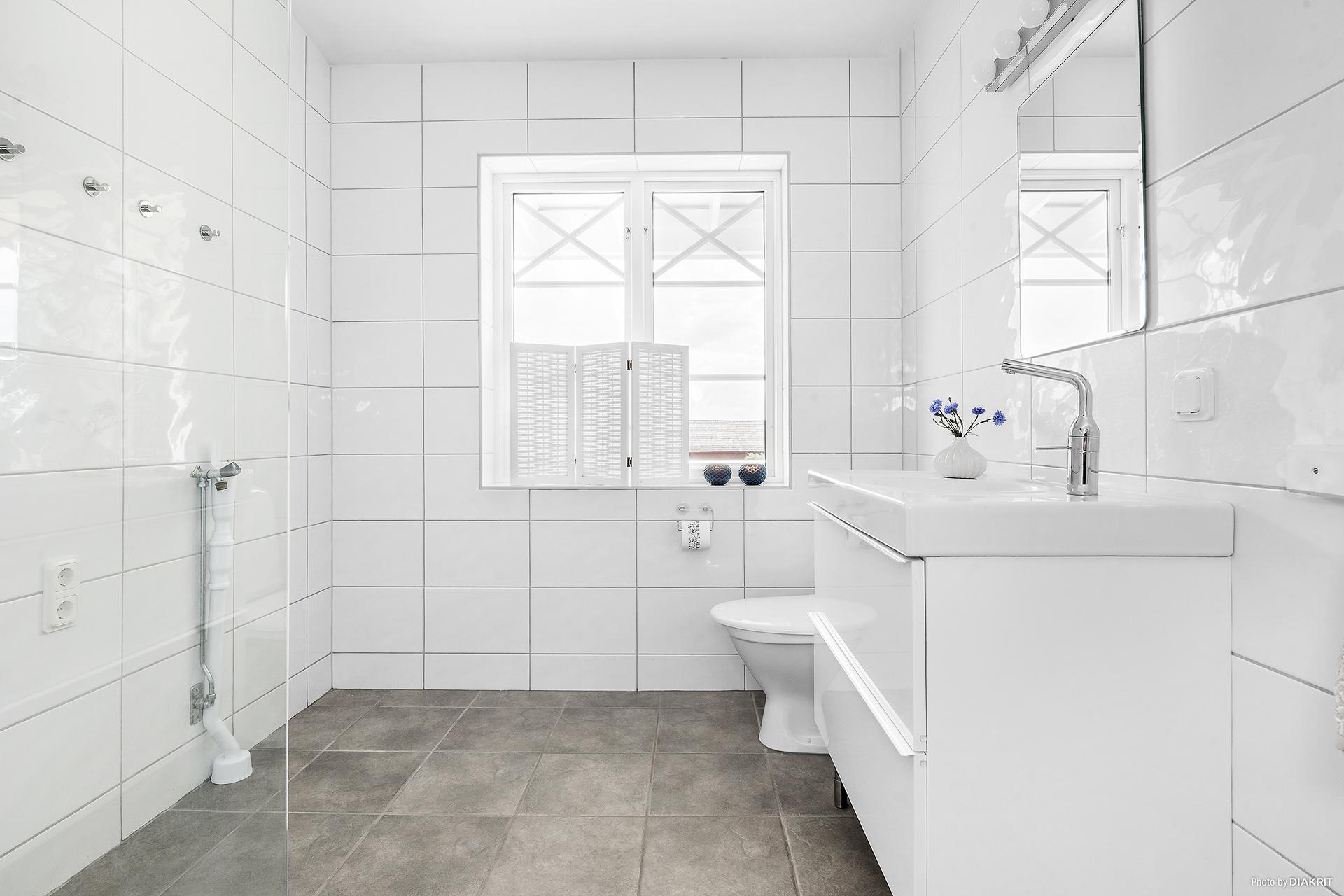 Nybyggt, elegant badrum. Helkaklat med grå klinkers (golvvärme) samt vitt kakel i liggande format.