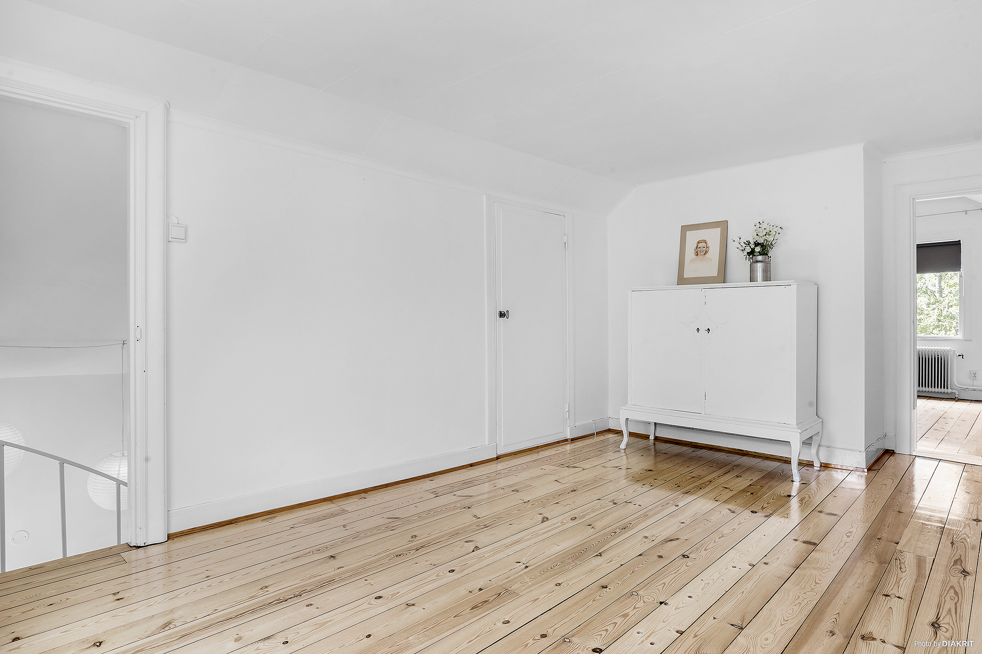 Allrum (eller sovrum) med trägolv och vitmålade väggar