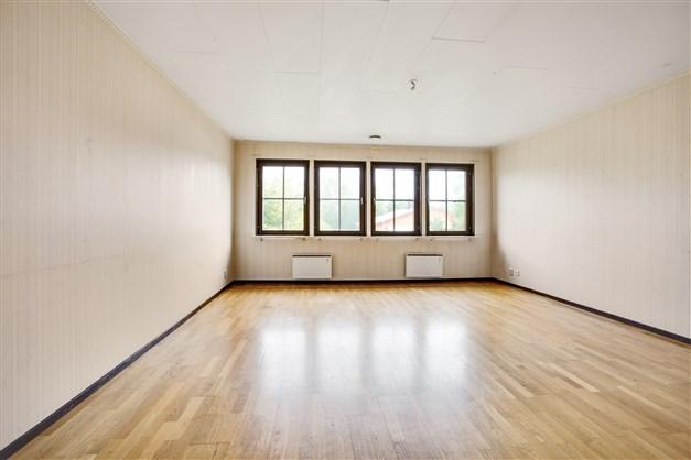 Lättmöblerat vardagsrum med flera fönster som ger fint ljus.