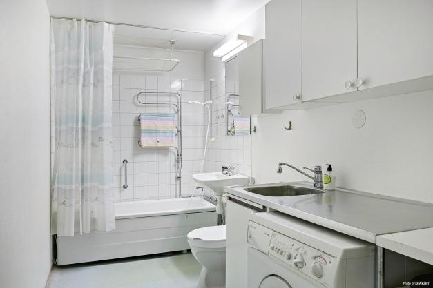 Rymligt badrum kombinerat med tvättavdelning.