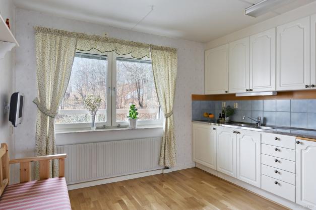 Välplanerat kök med naturlig plats för matbord framför fönsterpartiet.