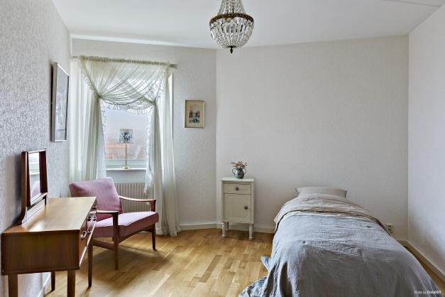 Rogivande sovrum med plats för bred säng, skrivbord samt garderob.