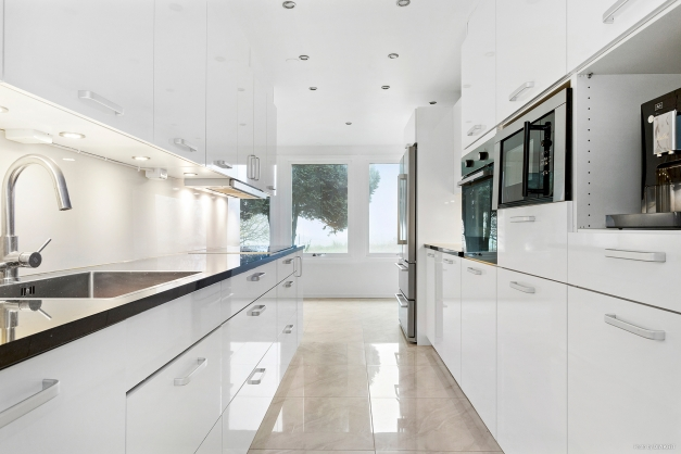Renoverat kök i högblank vitt.