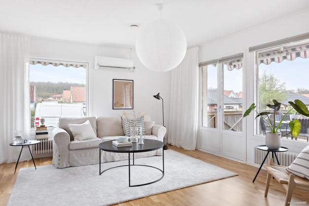 Vardagsrummet pryds av ljusa väggar och stora fönsterpartier som ger ett mycket fint ljusinsläpp.