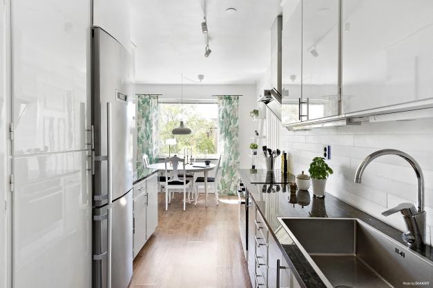 Ljust och fräscht kök med bänkskiva i sten och kakel i marmor
