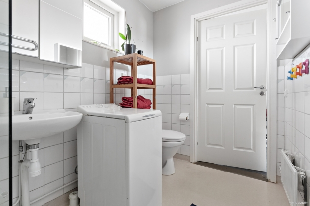 Badrum med toa, vask, dusch samt handdukstork.