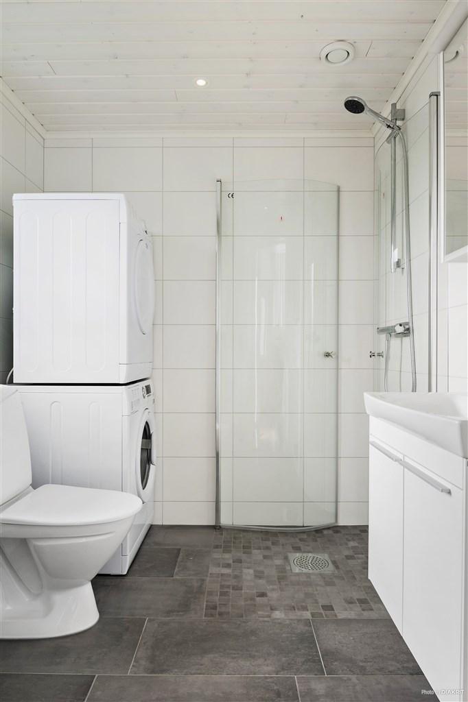 Grått klinker på golv och vitt kakel på väggarna. Elektrisk golvvärme. Utrustning: Dusch, WC, handfat med kommod (IFÖ på bild. Standard är HTH), spegelskåp, varmvattenberedare (Eminent). Tillval: Spotar, Tvättmaskin, Torktumlare, duschvägg