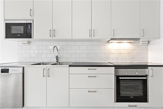 Fullt utrustade kök med vita luckor, kakel ovan arbetsbänk i laminat.